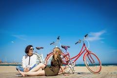 Deux amis s'asseyant sur la plage avec des bicyclettes Photos libres de droits