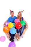 Deux amis s'asseyant sur le divan avec des chapeaux et des ballons Image stock