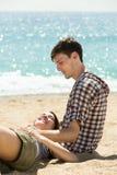 Deux amis s'asseyant sur le sable à la plage Photo stock