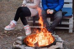 Deux amis s'asseyent autour d'un feu de camp et détendent, des randonneurs détendant près du feu de camp, fond de touristes Photographie stock