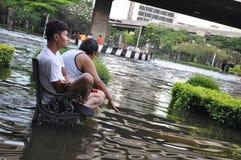 Deux amis s'asseyent sur un banc sous-marin dans une rue inondée à Bangkok, Thaïlande, en octobre 2011 Image stock