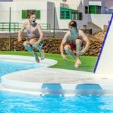 Deux amis sautant dans la piscine Photo libre de droits