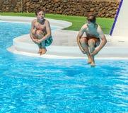 Deux amis sautant dans la piscine Photographie stock libre de droits