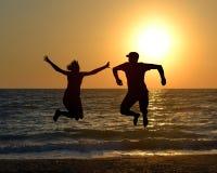 Deux amis sautant sur la plage pendant le lever de soleil Photos libres de droits