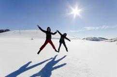 Deux amis sautent joyeux dans le ciel au-dessus de la neige Photographie stock