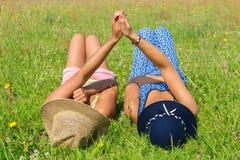 Deux amis se situant côte à côte dans l'herbe verte Images libres de droits