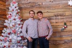 Deux amis se tiennent prêt l'arbre de Noël dans la chambre Image libre de droits