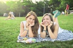 Deux amis se trouvant sur la pelouse Photo libre de droits