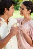 Deux amis souriant tout en se retenant et le glasse émouvant Image libre de droits