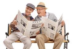 Deux amis supérieurs lisant les actualités Photographie stock libre de droits
