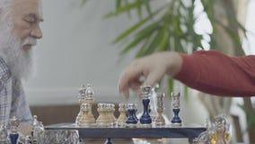 Deux amis supérieurs mûrs jouant la séance d'échecs à la maison Voisins caucasiens de vieux hommes jouant aux échecs joyeux à l'i clips vidéos