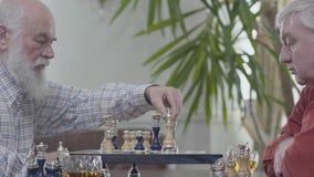 Deux amis supérieurs mûrs jouant la séance d'échecs à la maison Voisins caucasiens de vieux hommes jouant aux échecs joyeux à l'i banque de vidéos