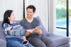Deux amis sur la ligne avec les dispositifs multiples et se reposer parlant sur un sofa Photo libre de droits