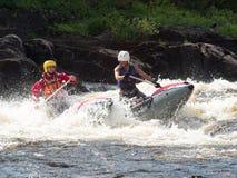 Deux amis sur un catamaran gonflable montent sur la rivière rugueuse Photographie stock libre de droits