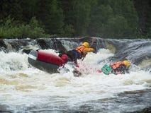 Deux amis sur un catamaran gonflable montent sur la rivière rugueuse Image stock