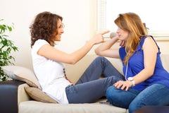 Deux amis sur un divan riant et ayant l'amusement Photo stock