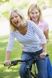 Deux amis sur un vélo souriant à l'extérieur Photos stock