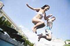 Deux amis tenant des mains et sautant dans une piscine, entre le ciel et la terre Photographie stock