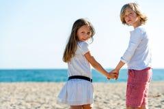 Deux amis tenant des mains sur la plage. Photos stock