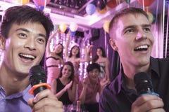 Deux amis tenant des microphones et chantant ensemble au karaoke, amis à l'arrière-plan Image libre de droits