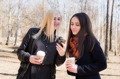 Deux amis tiennent les verres de papier et regardent le téléphone portable Image libre de droits