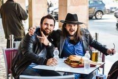 Deux amis/touristes affamés mangent dehors dans l'ouvert Images stock