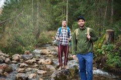 Deux amis trimardant par une rivière dans la forêt Images libres de droits