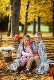 Deux amis : un garçon et une fille en automne garent se reposer sur le banc en bois près d'une barrière Photographie stock