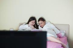 Deux amis utilisant des peignoirs observant un film effrayant sur le lit Photographie stock