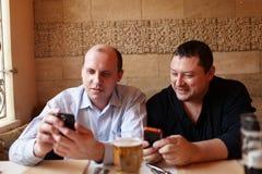 Deux amis à l'aide des téléphones portables Photos libres de droits