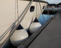 Deux amortisseurs blancs de bateau entre la couchette et le canot automobile Image libre de droits