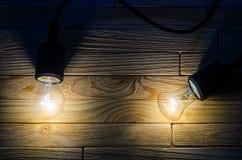 Deux ampoules brûlantes sur un fond en bois images libres de droits