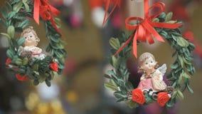 Deux anges de porcelaine sur les rubans rouges banque de vidéos