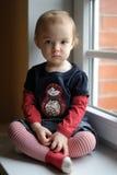 Deux années de fille d'enfant en bas âge par l'hublot Image stock