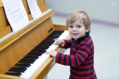 Deux années de garçon d'enfant en bas âge jouant le piano Photos stock