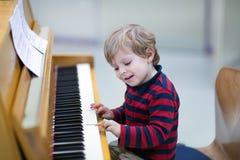 Deux années de garçon d'enfant en bas âge jouant le piano Images stock
