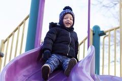 Deux années heureuses d'enfant en bas âge sur la glissière du ` s d'enfants Badine la cour de jeu Image libre de droits