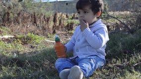 Deux années mignonnes d'eau potable de garçon de bouteille en nature banque de vidéos