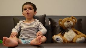 Deux ann?es mignonnes de gar?on regardant la TV avec son ours de nounours clips vidéos