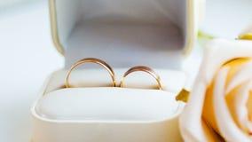 Deux anneaux d'or et roses blanches sur la table de la cérémonie de mariage banque de vidéos