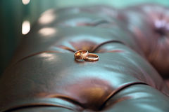 Deux anneaux d'or sur le sofa en cuir Photographie stock