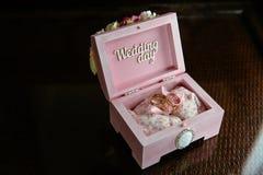 Deux anneaux dans une boîte avec l'inscription de jour du mariage sur la table foncée Concept de mariage Photographie stock