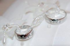 Deux anneaux de mariage d'or blanc sur la protection blanche de dentelle Photographie stock