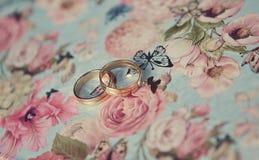 Deux anneaux de mariage d'or blanc sur les papillons bleus metal la boîte photo stock