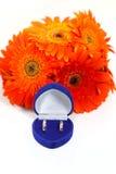Deux anneaux de mariage d'or avec un bouquet des gerberas oranges Images stock