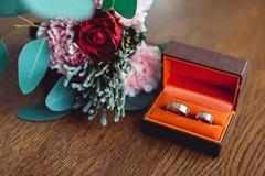 Deux anneaux de mariage d'or dans une boîte orange Photos stock