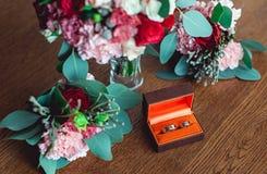 Deux anneaux de mariage d'or dans une boîte orange Photographie stock libre de droits