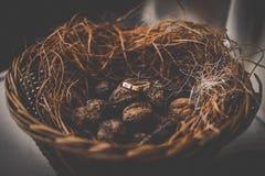 Deux anneaux de mariage d'or de luxe dans le panier rustique avec l'herbe sèche Photos stock