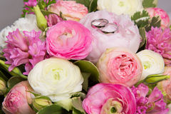 Anneaux de mariage sur le bouquet des pivoines blanches et roses Images stock