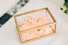 Deux anneaux de mariage d'or sur un cercueil en verre Jour du mariage image stock